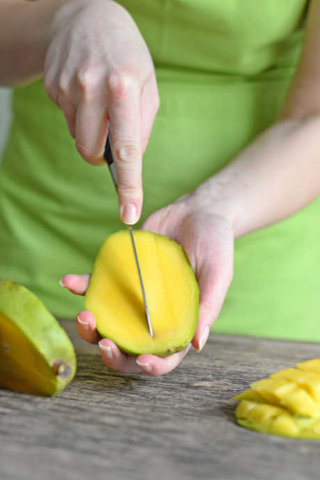 Slice the mango on either side of the midline, eliminating about a 1/2-inch section with the stem at the top. That's the pit; the rest of the mango is edible. Then score each half of the mango into cubes, as you might do with an avocado, and scoop the flesh out of the skin.